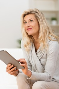 Woman using a tablet sitting thinking looking pensively up into the air with her finger poised over the touch screen